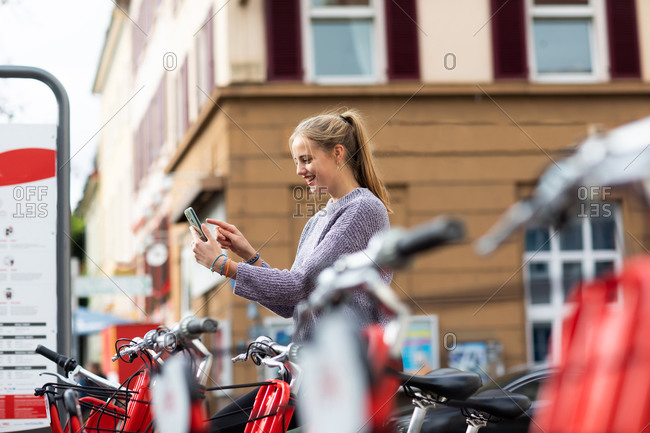 Young woman using rental bike in the city with smart phone