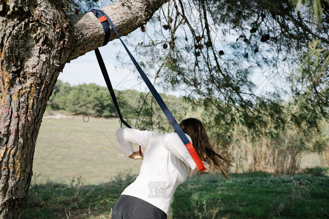 TRX sport team. Young woman doing exercises outdoors in a park. Strap