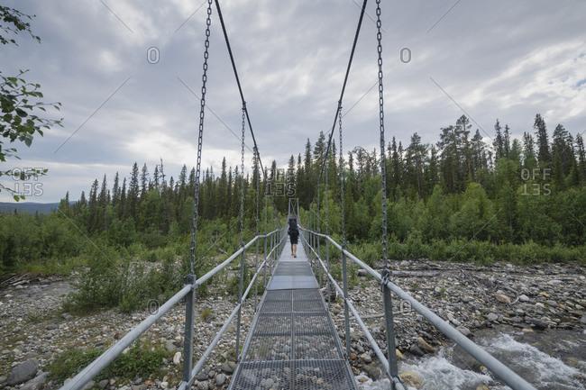 Hiker walking across hanging bridge over small river on Padjelantaleden Trail, Lapland, Sweden