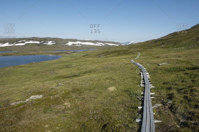 Wooden boardward protecting terrain around high alpine lakes along Padjelantaleden Trail near Duottar, Lapland, Sweden