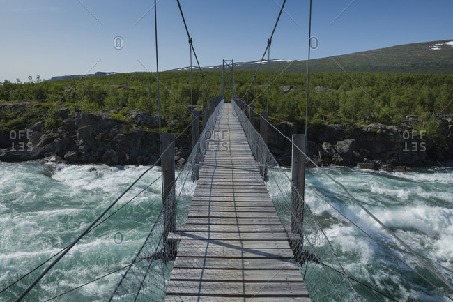 Hanging bridge over flowing water of Vuojatadno river along Padjelantaleden Trail, Lapland, Sweden