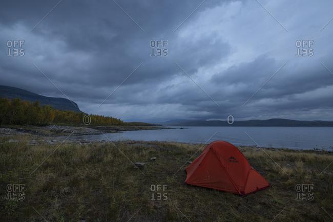 Jakkvik, Norrbotten County, Sweden - September 11, 2019: Tent wild camping beneath heavy clouds on the shore of lake Riebnes, Kungsleden Trail, Lapland, Sweden