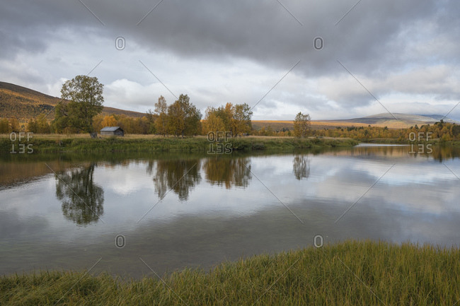 Reflection of trees in river delta at Baverholmen along Kungsleden Trail, Lapland, Sweden
