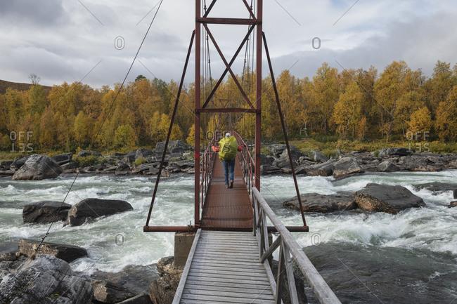 Hiker crossing hanging bridge over Lajsso river along Kungsleden Trail, Lapland, Sweden