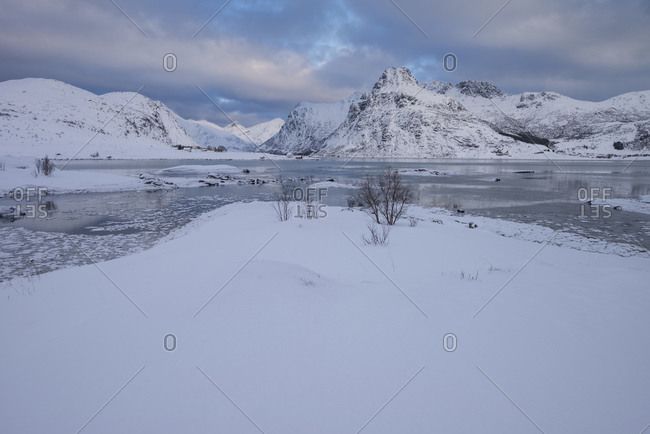 Ice filled bay with distant mountains at Flakstadpollen, Flakstadoy, Lofoten Islands, Noway