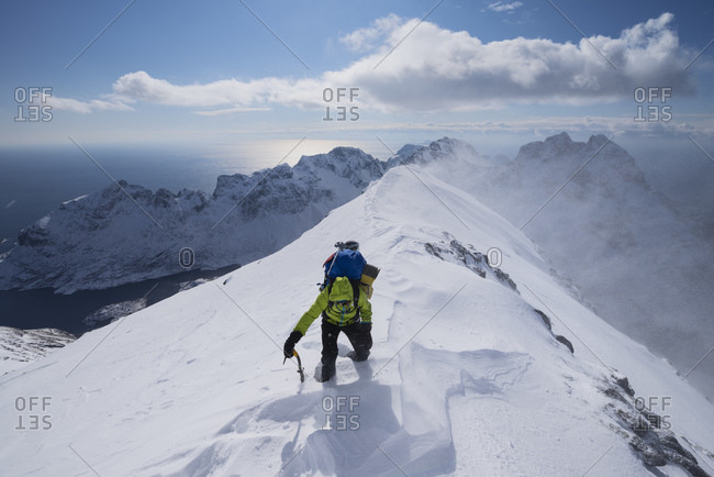 A, Nordland, Norway - April 13, 2017: Female hiker approaching summit of Mengensdalstind in deep snow and high wind, Moskenesoy, Lofoten Islands, Norway