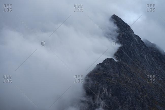 Misty clouds blow over mountain ridge, Senja, Norway