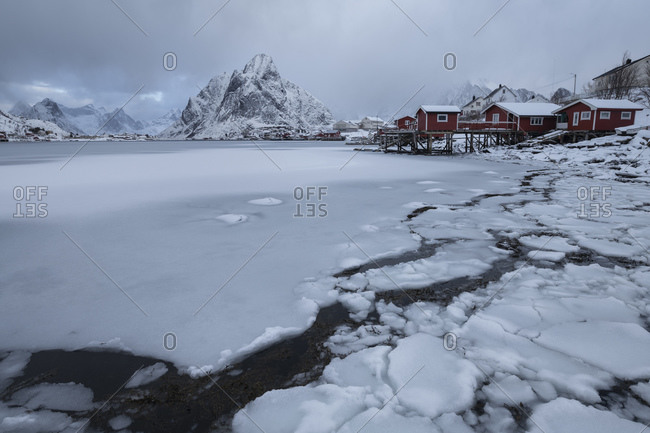 Reine, Nordland, Norway - March 6, 2019: Olstind mountain peak rises over frozen bay at Reine, Moskenesoy, Lofoten Islands, Norway