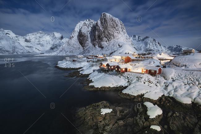 Full moon illuminates snow covered landscape and village of Hamnoy, Moskenesoy, Lofoten Islands, Norway