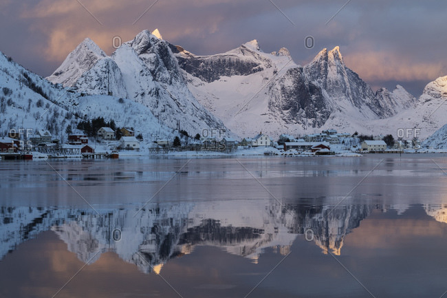 Low January sun illuminates distant mountain peaks across Reinefjord, Reine, Moskenesoy, Lofoten Islands, Norway