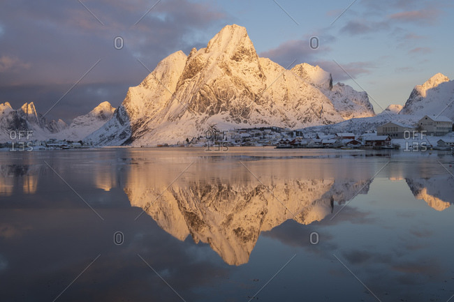 Reine, Nordland, Norway - January 21, 2019: Olstind mountain peak lit in January winter sunlight, Reine, Moskenesoy, Lofoten Islands, Norway
