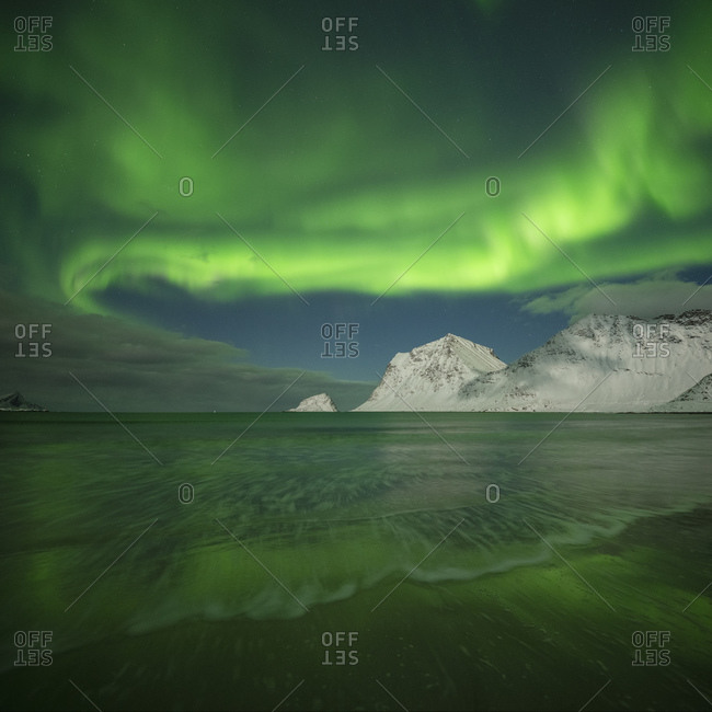 Northern lights - aurora borealis shine in sky over Vik beach and snowy mountains, Vestvagoy, Lofoten Islands, Norway