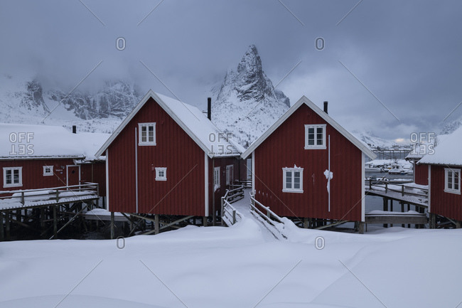 Red rorbu cabins below mountain peak in winter, Reine, Moskenesoy, Lofoten Islands, Norway