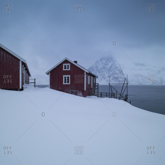 Olstind mountain peak and red rorbu cabins rising over snow covered coastline, Moskenesoy, Lofoten Islands, Norway