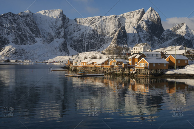 Winter morning light shines on yellow rorbu cabins at Sakrisoy, Moskenesoy, Lofoten Islands, Norway