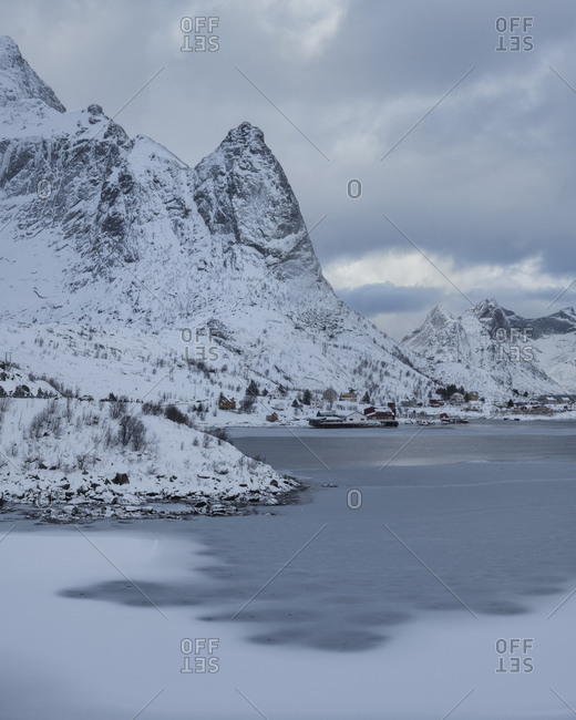 Mountains rise above frozen bay in Reine harbor, Reine, Moskenesoy, Lofoten Islands, Norway