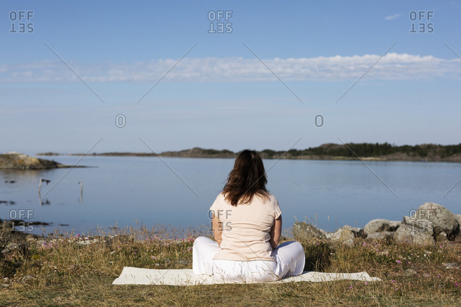 Woman meditating at sea from the Offset collection