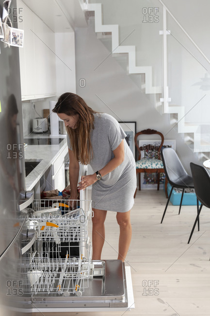 Pregnant woman emptying dishwasher from the Offset collection