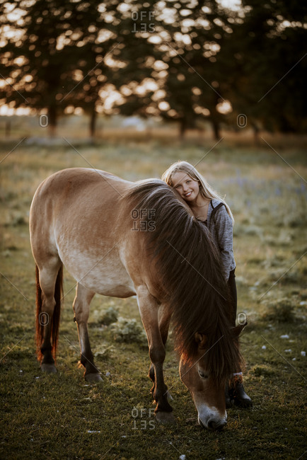 Smiling girl hugging pony from the Offset collection