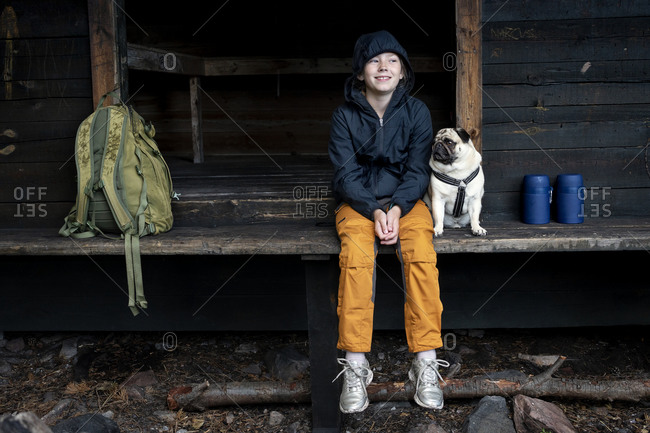 Girl with pug sitting by wooden building