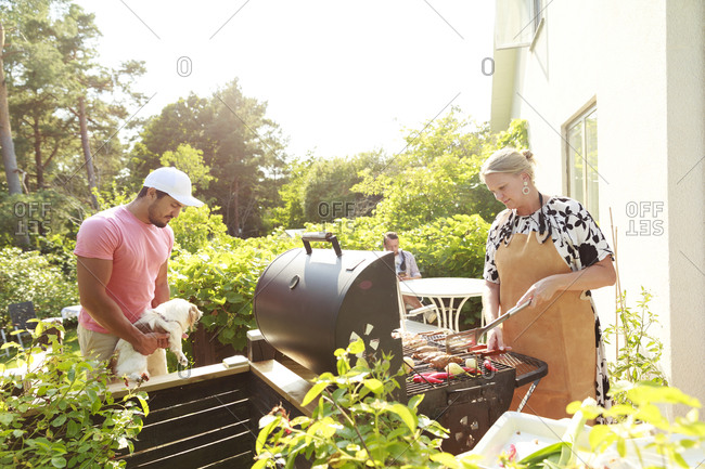 Couple in garden, woman preparing food on barbecue