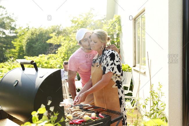Man kissing woman near barbecue