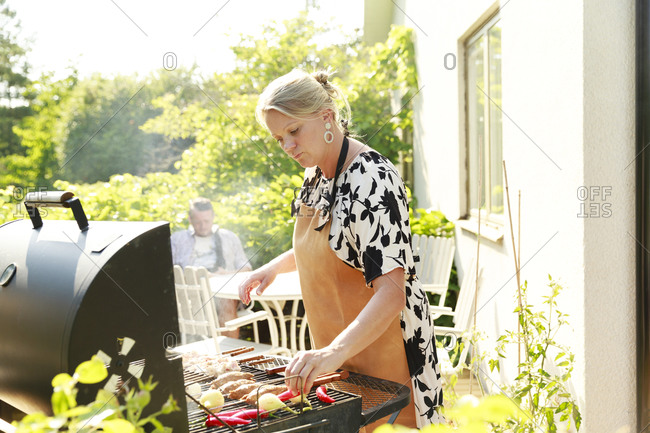 Woman preparing food on barbecue in garden