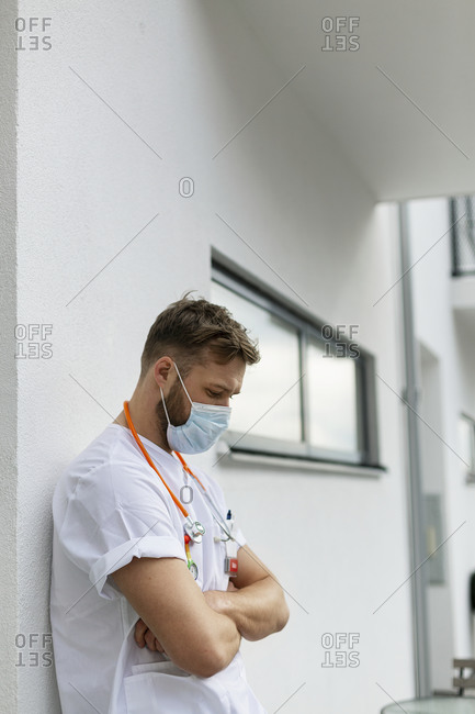 Tired male doctor in front of building