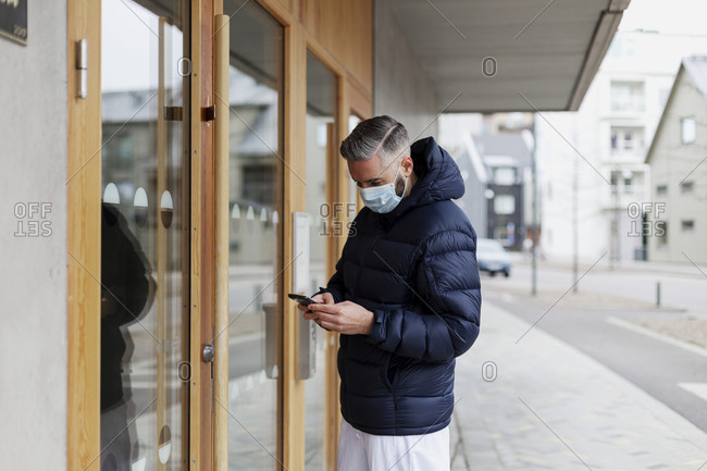 Man wearing face mask using phone in front of entrance door