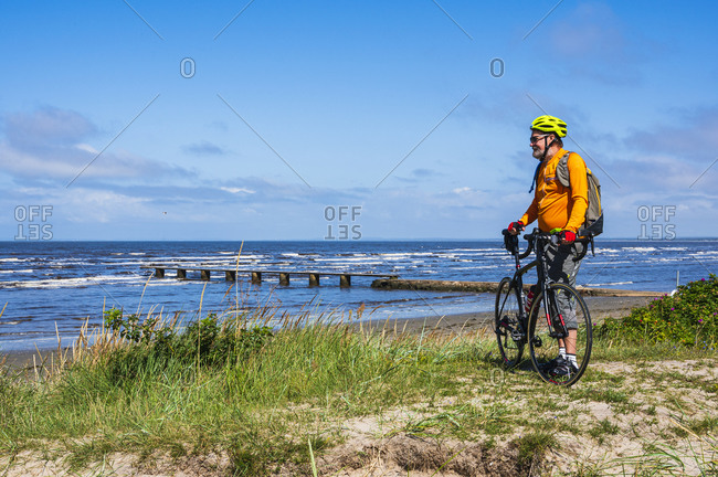 Man holding bicycle and looking at sea