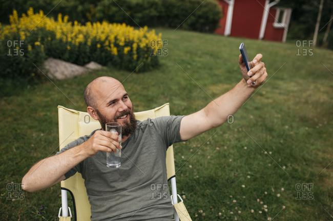 Man on deck chair taking selfie
