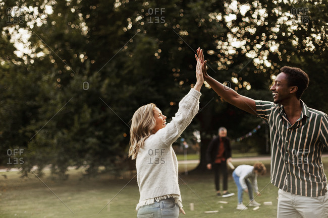 Friends in park giving each other high five