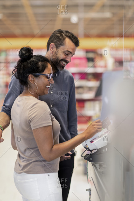 Smiling couple paying at till
