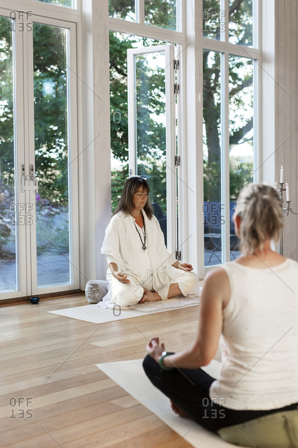 Yoga teacher sitting in front of class
