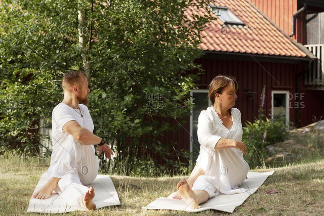 Man and woman practicing yoga at summer