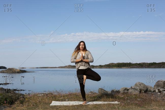 Woman doing yoga at sea