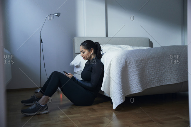 Woman sitting on bedroom floor and using phone