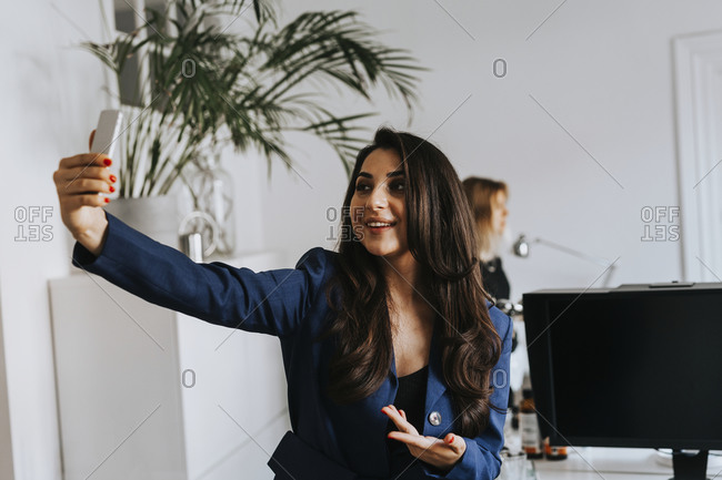 Smiling woman taking selfie in office