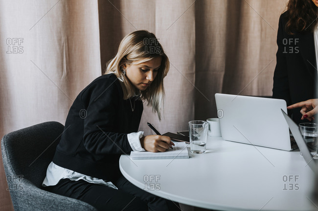 Woman in office taking notes