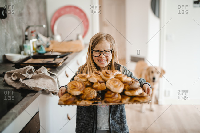 Smiling girl holding tray with cinnamon buns