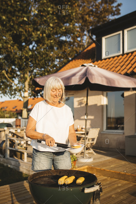 Woman in garden having barbecue
