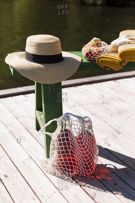 Bottles in net bag and straw hat on jetty