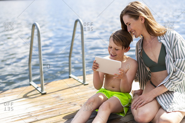 Mother with son on jetty looking at digital tablet