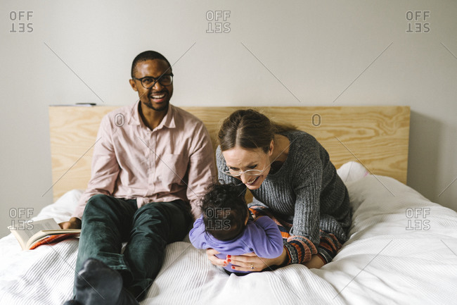 Parents with baby on bed