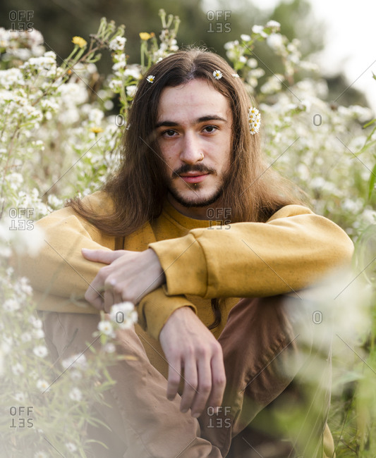 Romantic young long haired male in casual outfit sitting amidst blooming wildflowers and looking at camera while resting in summer countryside