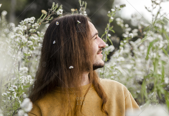 Side view of romantic young long haired male in casual outfit sitting amidst blooming wildflowers and looking away while resting in summer countryside