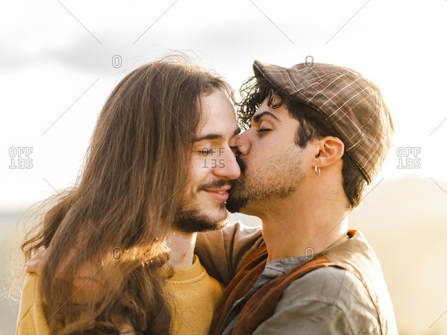 Passionate young ethnic boyfriends embracing and kissing each other while having intimate moments during romantic date in nature