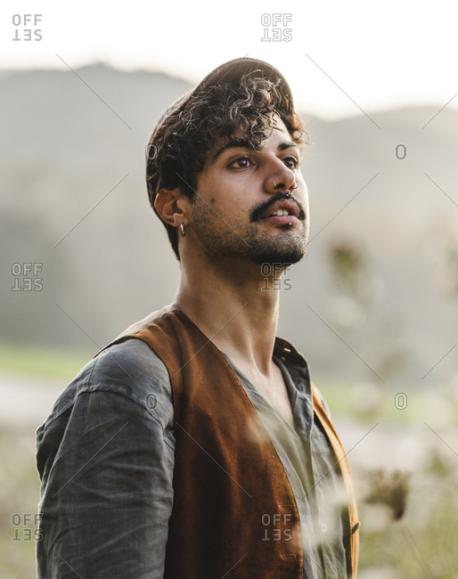 Dreamy young curly haired bearded ethnic male with piercing in ear wearing stylish clothes and cap looking away while standing on green meadow against blurred mountains