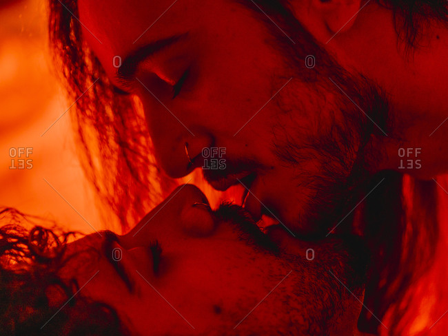 Closeup side view of passionate kissing homosexual male couple kissing gently in red illumination