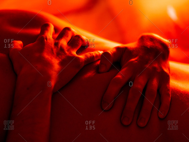 Crop anonymous homosexual male partners having passionate moments in bed in red illumination